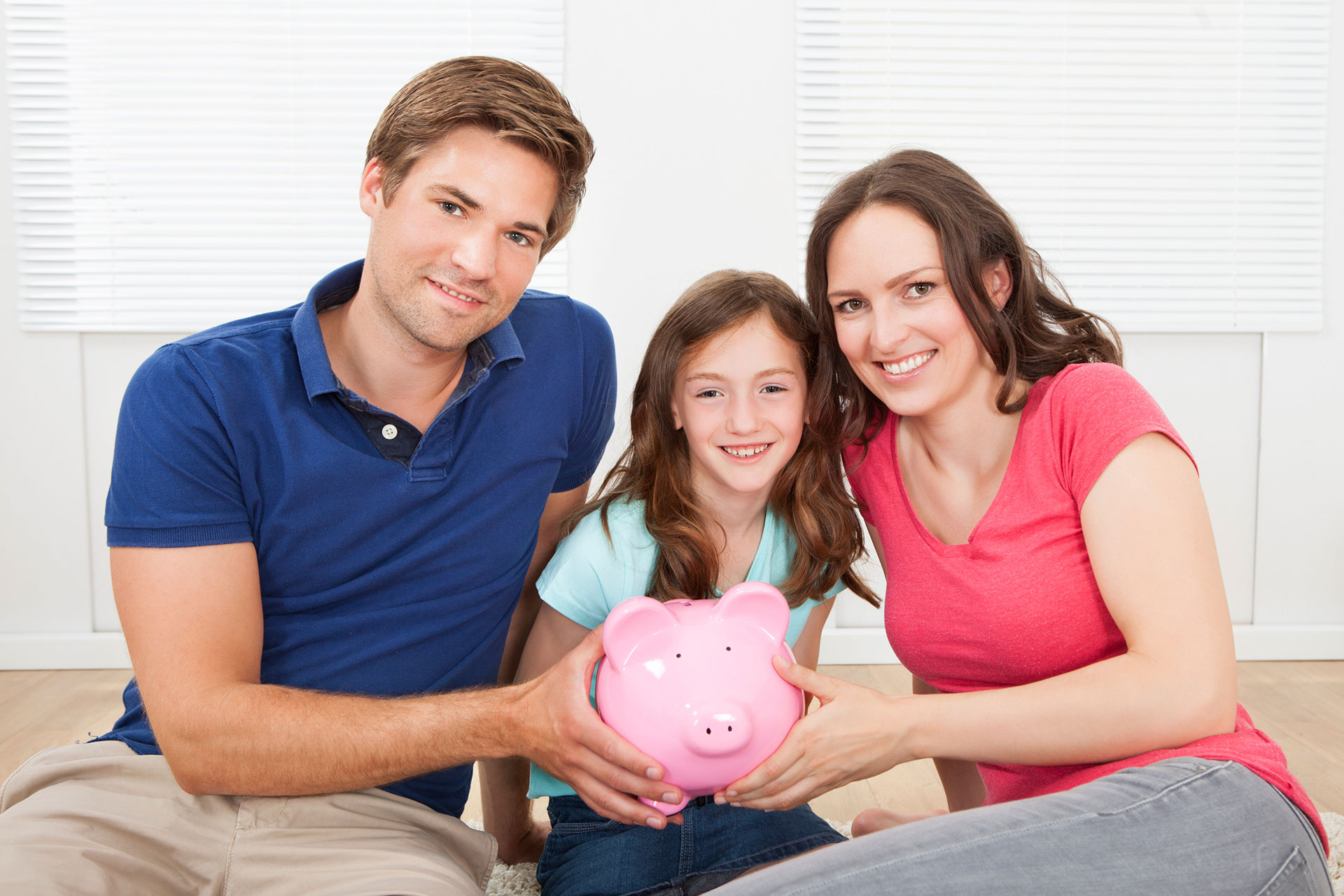Mom and dad with young girl and piggy bank